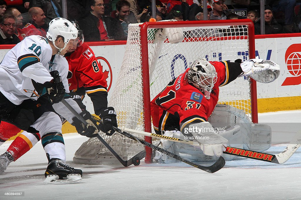 Karri Ramo #31 and Joe Colborne #8 of the Calgary Flames defend the net against Andrew Desjardins #10 of the San Jose Sharks at Scotiabank Saddledome on March 24, 2014 in Calgary, Alberta, Canada.