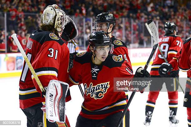 Karri Ramo and Johnny Gaudreau of the Calgary Flames celebrate a 41 win over the Winnipeg Jets after an NHL game at Scotiabank Saddledome on December...