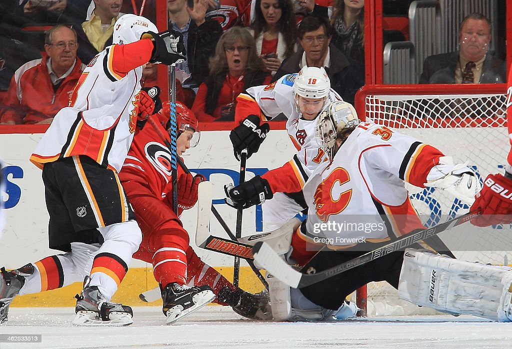 <a gi-track='captionPersonalityLinkClicked' href=/galleries/search?phrase=Karri+Ramo&family=editorial&specificpeople=716721 ng-click='$event.stopPropagation()'>Karri Ramo</a> #31 of the Calgary Flames defends the net as <a gi-track='captionPersonalityLinkClicked' href=/galleries/search?phrase=Jeff+Skinner&family=editorial&specificpeople=3147596 ng-click='$event.stopPropagation()'>Jeff Skinner</a> #53 of the Carolina Hurricanes battles against Matt Stajan #18 during their NHL game at PNC Arena on January 13, 2014 in Raleigh, North Carolina.