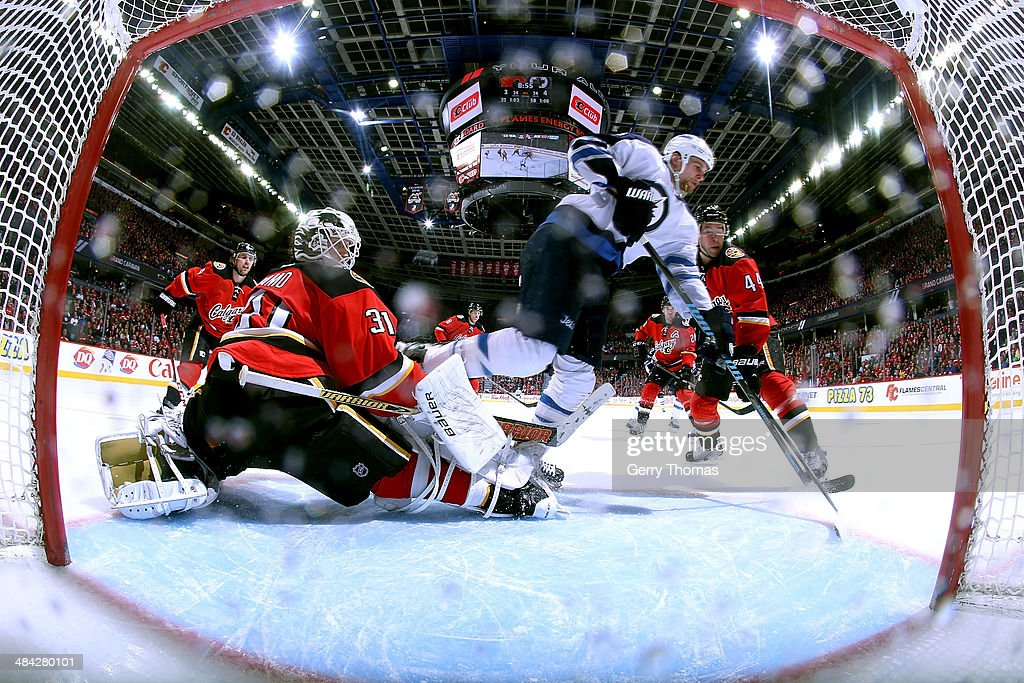 Karri Ramo #31 of the Calgary Flames makes a save against Adam Pardy #2 of the Winnipeg Jets at Scotiabank Saddledome on April 11, 2014 in Calgary, Alberta, Canada.
