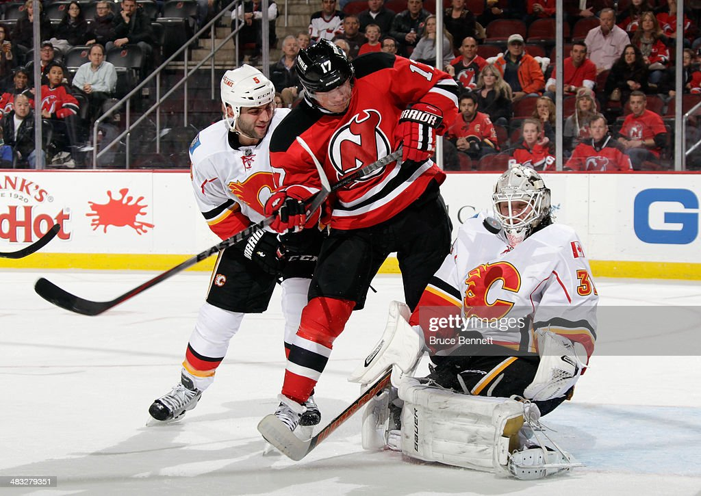 Karri Ramo #31 of the Calgary Flames makes the second period save as Michael Ryder #17 of the New Jersey Devils is checked by Mark Giordano #5 at the Prudential Center on April 7, 2014 in Newark, New Jersey.