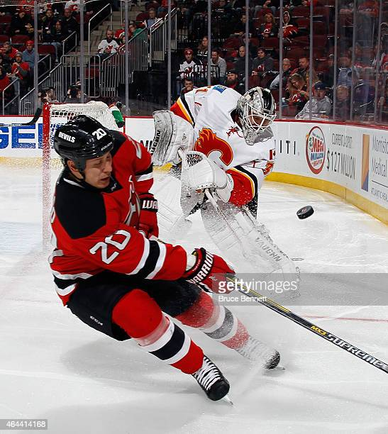 Karri Ramo of the Calgary Flames shoots the puck away from the onrushing Jordin Tootoo of the New Jersey Devils during the second period at the...