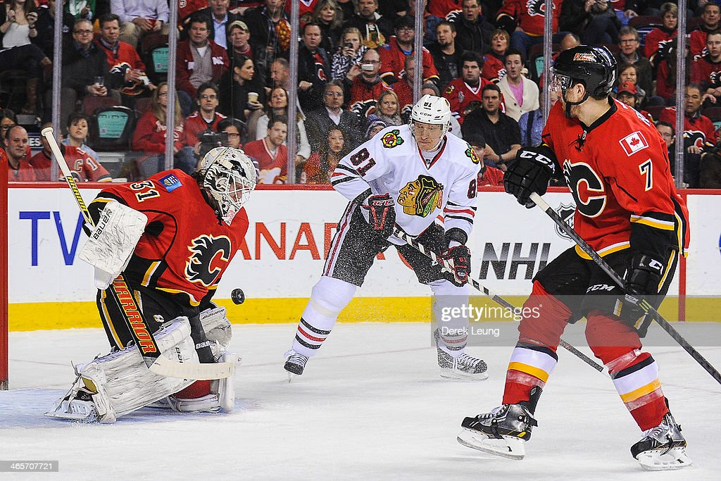 <a gi-track='captionPersonalityLinkClicked' href=/galleries/search?phrase=Karri+Ramo&family=editorial&specificpeople=716721 ng-click='$event.stopPropagation()'>Karri Ramo</a> #31 of the Calgary Flames stops the shot of <a gi-track='captionPersonalityLinkClicked' href=/galleries/search?phrase=Marian+Hossa&family=editorial&specificpeople=202233 ng-click='$event.stopPropagation()'>Marian Hossa</a> #81 of the Chicago Blackhawks during an NHL game at Scotiabank Saddledome on January 28, 2014 in Calgary, Alberta, Canada. The Flames defeated the Blackhawks 5-4 in overtime.