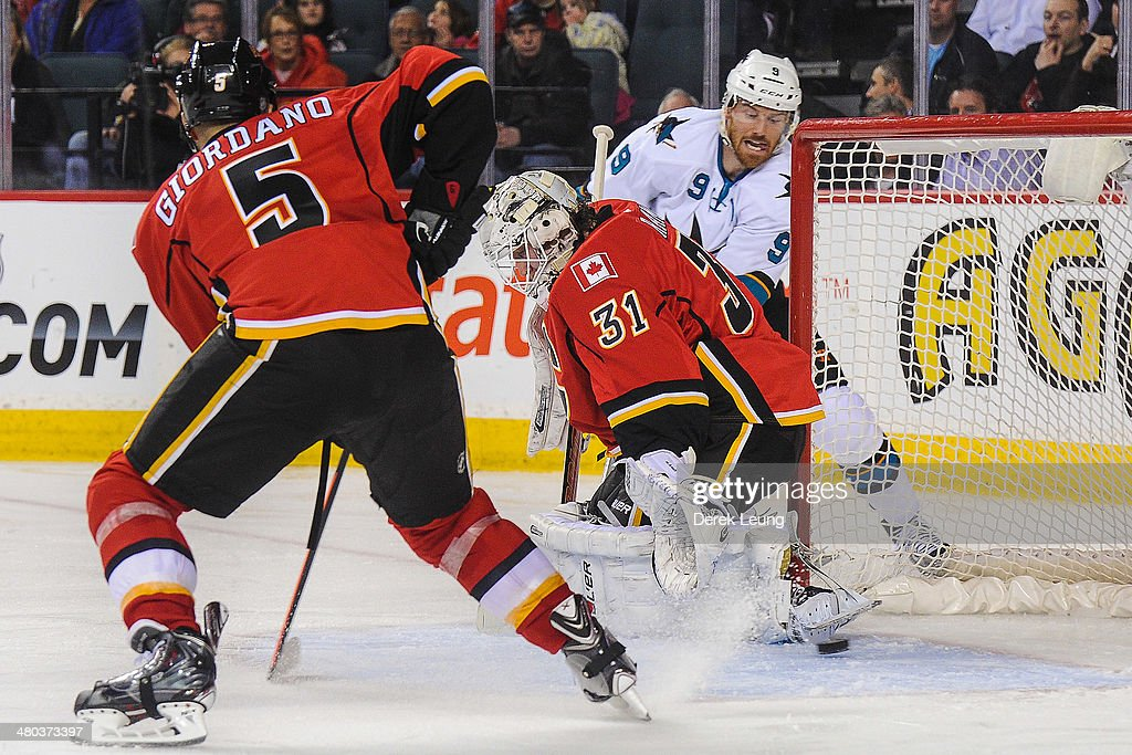 Karri Ramo #31 of the Calgary Flames stops the shot of Martin Havlat #9 of the San Jose Sharks during an NHL game at Scotiabank Saddledome on March 24, 2014 in Calgary, Alberta, Canada.