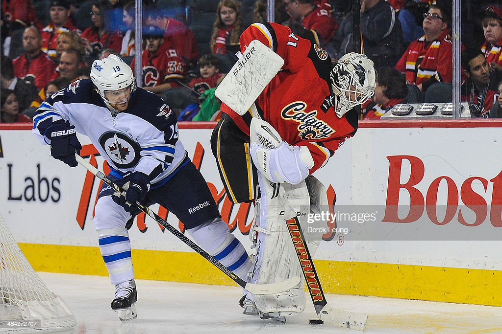 Karri Ramo #31 of the Calgary Flames tries to pass the puck up as Jim Slater #19 of the Winnipeg Jets attempts to check him during an NHL game at Scotiabank Saddledome on April 11, 2014 in Calgary, Alberta, Canada.