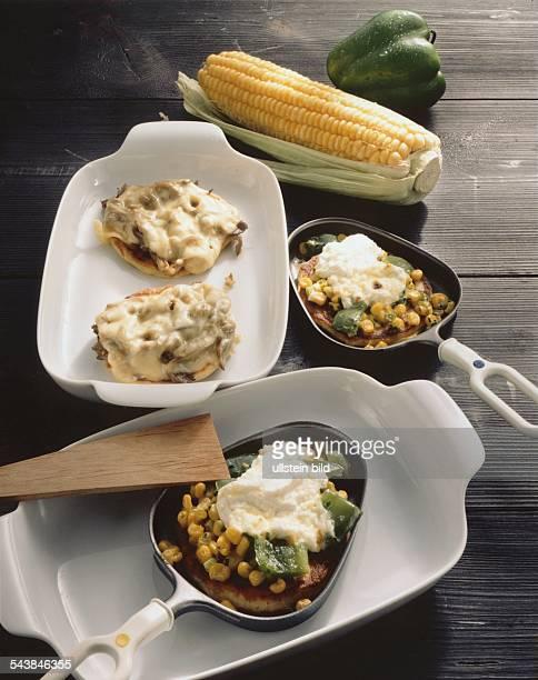 Kartoffelplinsen mit Mais grünem Paprika und Crème Fraîche in Racletteformen daneben in einer Schüssel Kartoffelplinsen mit Pilzen und Käse...