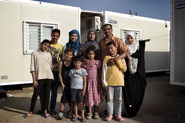Kasem Alsabsabi (2R), 45, with his wife Rafa (3R) and their children pose at the refugee camp of Skaramangas, an industrial area near the port of Piraeus on June 28, 2016, during a 14-day visit of ...