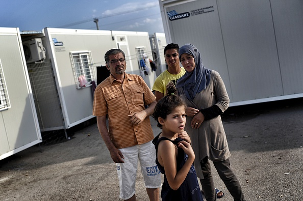 Kasem Alsabsabi (L), 45, with his wife Rafa (R) and two of their children stand at the refugee camp of Skaramangas, an industrial area near the port of Piraeus on June 28, 2016, during a 14-day vis...