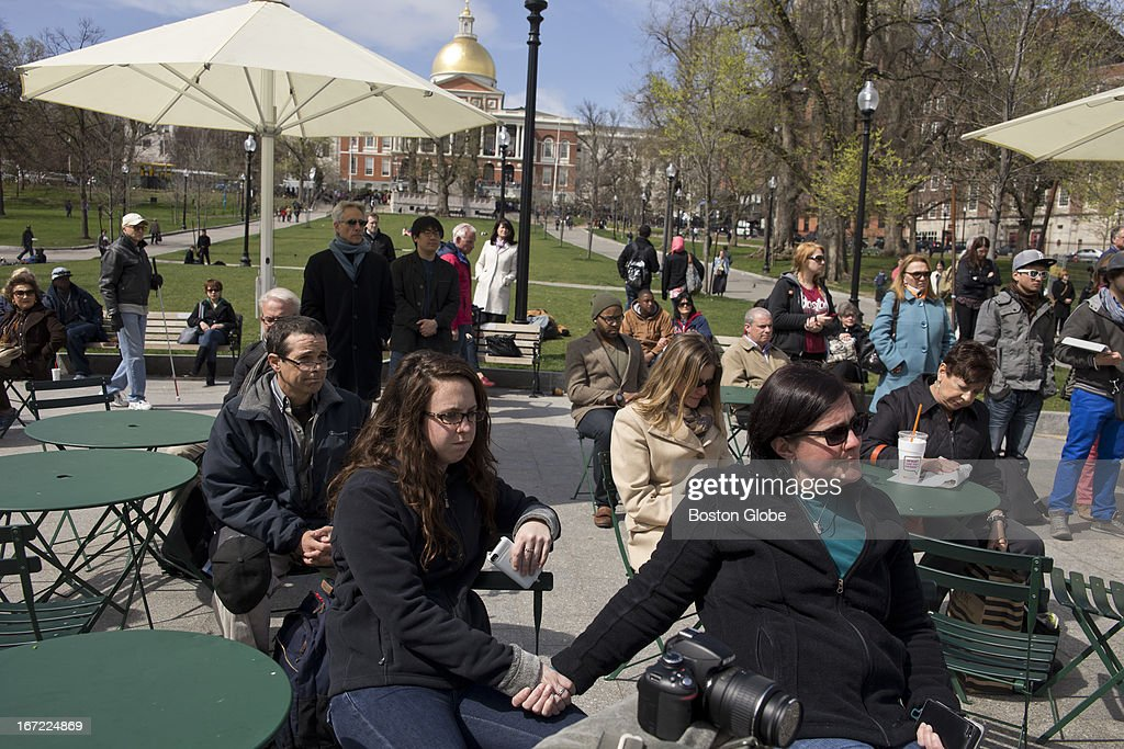 Kasey Finn, left, and Lori Magno of Boston, hold hands while observing a moment of silence for the victims of the Boston Marathon bombings. After, a group of orchestra students from the New England Conservatory performed Beethoven in the Boston Common near Park Street Station, on Monday, April 22, 2013.
