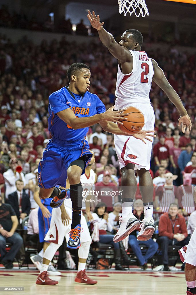 Kasey Hill #0 of the Florida Gators makes a pass from underneath the basket past Alandise Harris #2 of the Arkansas Razorbacks at Bud Walton Arena on January 11, 2014 in Fayetteville, Arkansas. The Gators defeated the Razorbacks 84-82.
