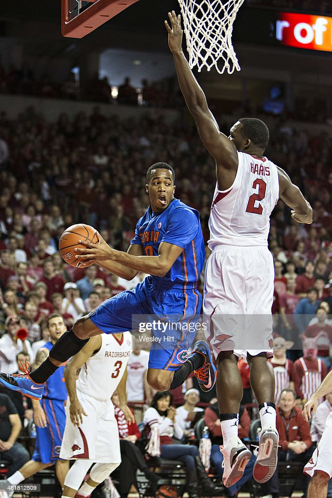 Kasey Hill #0 of the Florida Gators passes out from underneath the basket while being defended by Alandise Harris #2 of the Arkansas Razorbacks at Bud Walton Arena on January 11, 2014 in Fayetteville, Arkansas.