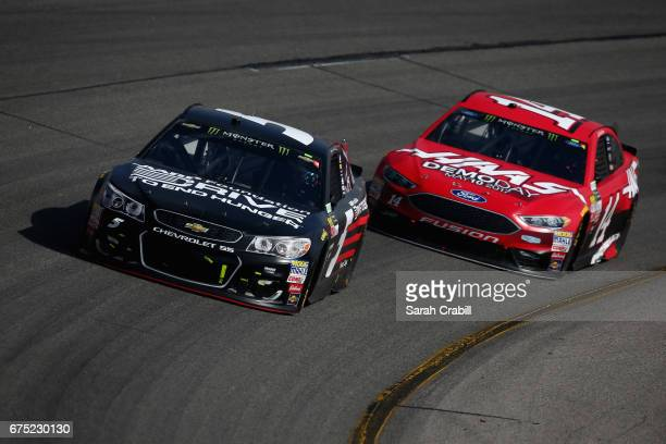 Kasey Kahne driver of the AARP Drive to End Hunger Chevrolet leads Clint Bowyer driver of the Haas Automation Demo Days Ford during the Monster...