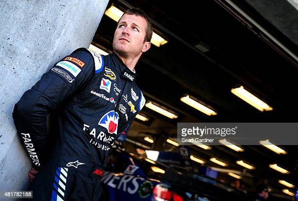 Kasey Kahne driver of the Farmers Chevrolet stands in the garage area during practice for the NASCAR Sprint Cup Series Crown Royal Presents the Jeff...