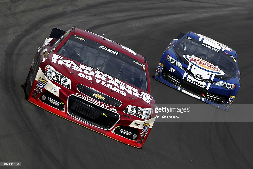 Kasey Kahne, driver of the #5 Farmers Insurance 85th Anniversary Chevrolet, leads Travis Kvapil, driver of the #93 Burger King/Dr. Pepper Toyota, during the NASCAR Sprint Cup Series STP 400 at Kansas Speedway on April 21, 2013 in Kansas City, Kansas.