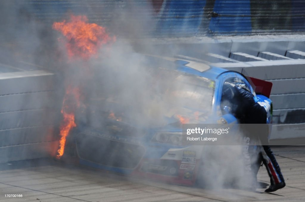 Kasey Kahne, driver of the #5 Farmers Insurance Chevrolet, climbs from his car after an incident during the NASCAR Sprint Cup Series Quicken Loans 400 at Michigan International Speedway on June 16, 2013 in Brooklyn, Michigan.
