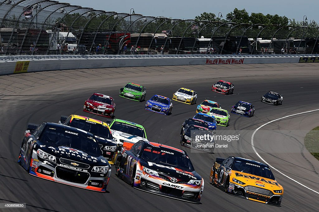 Kasey Kahne, driver of the #5 Farmers Insurance Chevrolet, Denny Hamlin, driver of the #11 FedEx Express Toyota, and Marcos Ambrose, driver of the #9 DeWalt Ford, race ahead of a pack of cars during the NASCAR Sprint Cup Series Quicken Loans 400 at Michigan International Speedway on June 15, 2014 in Brooklyn, Michigan.