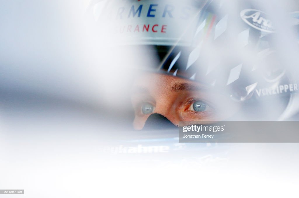 Kasey Kahne driver of the Farmers Insurance Chevrolet looks on from his car during practice for the NASCAR Sprint Cup AAA 400 Drive For Autism at...