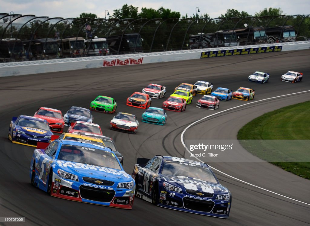 Kasey Kahne, driver of the #5 Farmers Insurance Chevrolet, races Jimmie Johnson, driver of the #48 Lowe's Chevrolet, during the NASCAR Sprint Cup Series Quicken Loans 400 at Michigan International Speedway on June 16, 2013 in Brooklyn, Michigan.