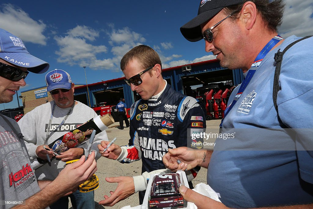 Kasey Kahne, driver of the #5 Farmers Insurance Chevrolet, signs autographs during practice for the NASCAR Sprint Cup Series Geico 400 at Chicagoland Speedway on September 13, 2013 in Joliet, Illinois.