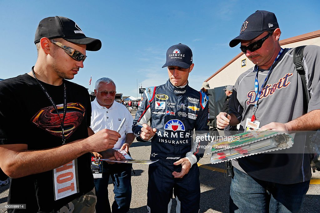 Kasey Kahne, driver of the #5 Farmers Insurance Chevrolet, signs his autograph for fans in the garage area during practice for the NASCAR Sprint Cup Series Quicken Loans 400 at Michigan International Speedway on June 14, 2014 in Brooklyn, Michigan.