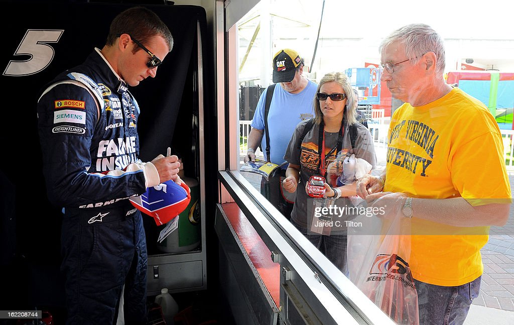 Kasey Kahne (L), driver of the #5 Farmers Insurance Chevrolet, signs his autograph in the garage during practice for the NASCAR Sprint Cup Series Daytona 500 at Daytona International Speedway on February 20, 2013 in Daytona Beach, Florida.
