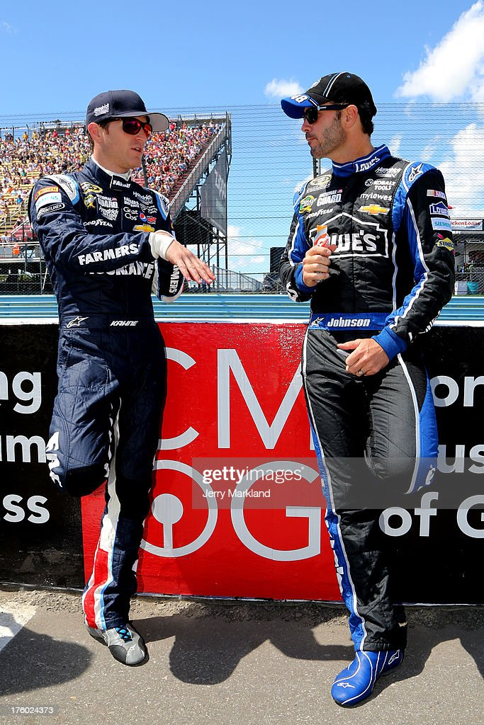Kasey Kahne, driver of the #5 Farmers Insurance Chevrolet, talks with Jimmie Johnson, driver of the #48 Lowe's Chevrolet, on the grid during pre-race ceremonies for the NASCAR Sprint Cup Series Cheez-It 355 at The Glen at Watkins Glen International on August 11, 2013 in Watkins Glen, New York.