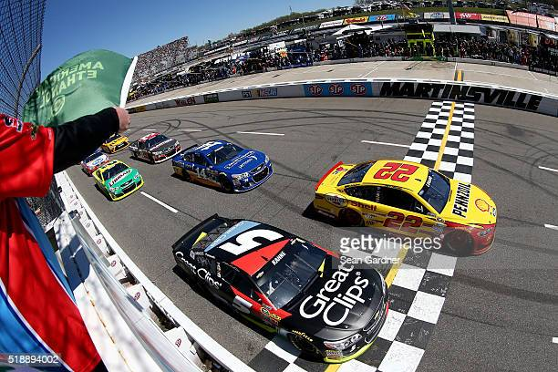 Kasey Kahne driver of the Great Clips Chevrolet and Joey Logano driver of the Shell Pennzoil Ford lead the field at the start of the NASCAR Sprint...