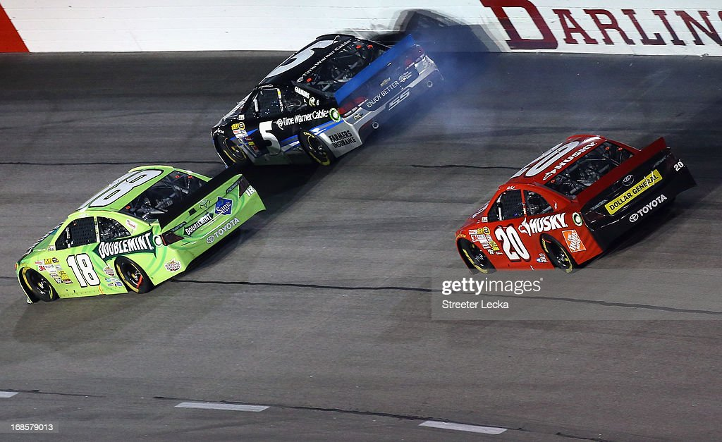 Kasey Kahne, driver of the #5 Time Warner Cable Chevrolet, hits the ball as Kyle Busch, driver of the #18 Double Mint Gum Toyota, and Matt Kenseth, driver of the #20 The Home Depot / Husky Toyota, try to get out of the way during the NASCAR Sprint Cup Series Bojangles' Southern 500 at Darlington Raceway on May 11, 2013 in Darlington, South Carolina.