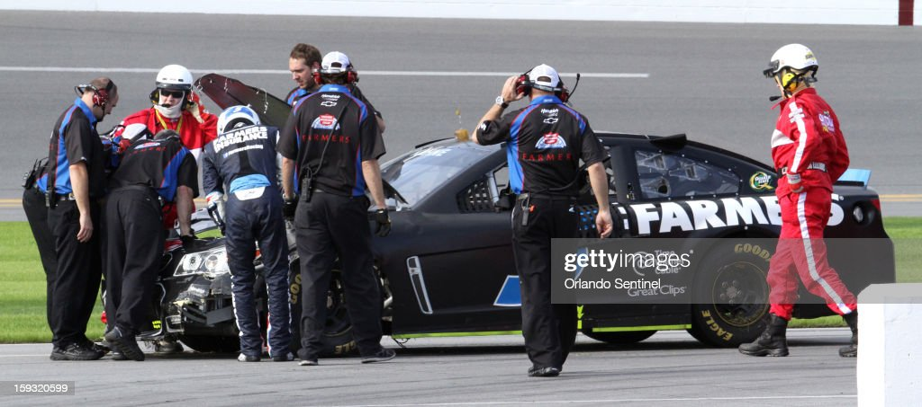 Kasey Kahne's crew assists his return the garage after his crash in a 12-car pile-up during test trials at Daytona International Speedway in Daytona Beach, Florida, Friday, January 11, 2013.