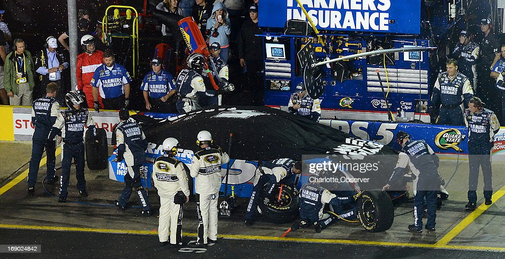 Kasey Kahne's crew make adjustments to the car as rain falls on the NASCAR Sprint All-Star race at Charlotte Motor Speedway on Saturday, May 18, 2013, in Concord, North Carolina. The race was red flagged at lap 13 due to rain.