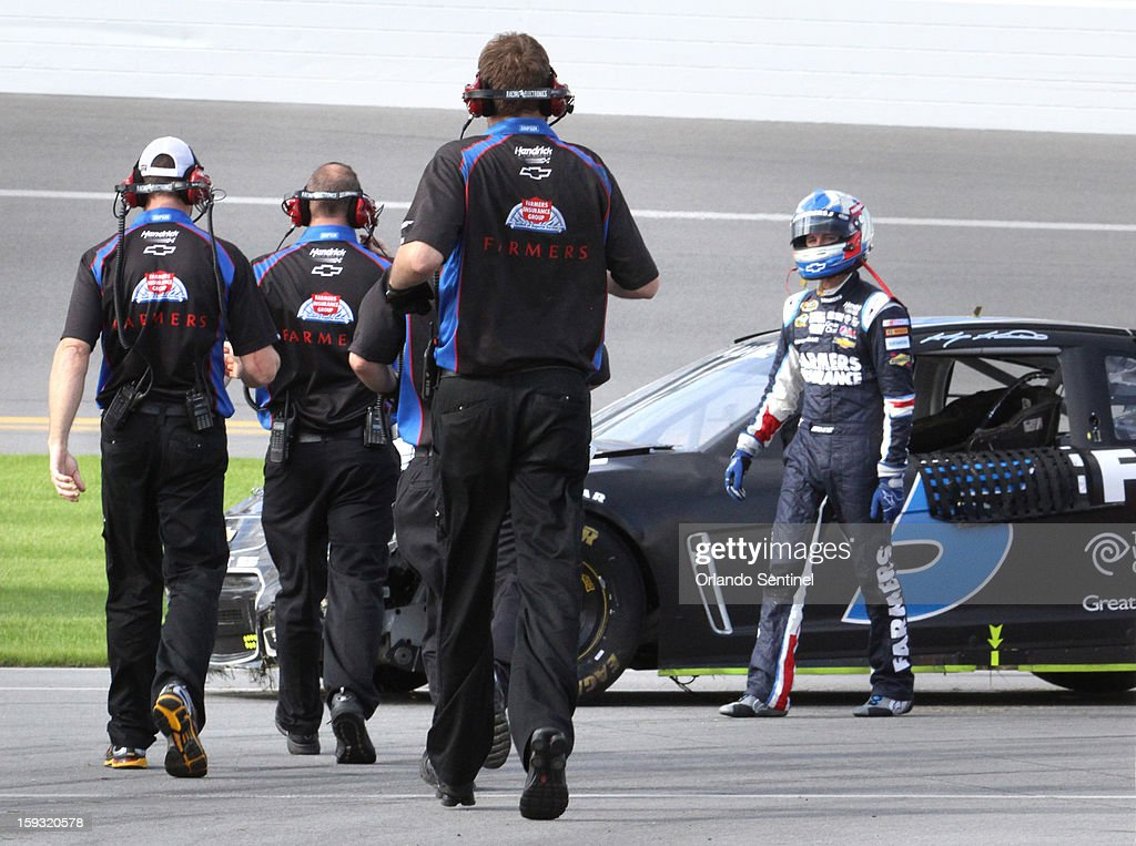 Kasey Kahne's crew runs to assist his return the garage after he crashed in a 12-car pile-up during test trials at Daytona International Speedway in Daytona Beach, Florida, Friday, January 11, 2013.
