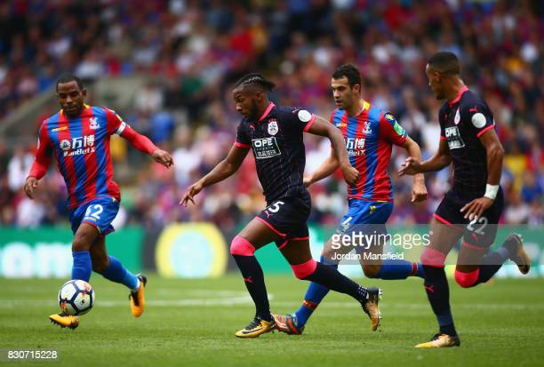 Kasey Palmer of Huddersfield Town attempts to get away from Luka Milivojevic of Crystal Palace during the Premier League match between Crystal Palace...