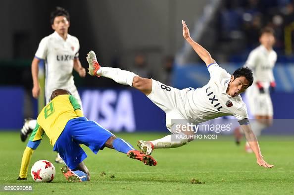 Kashima Antlers forward Shuhei Akasaki falls as he crashes with Mamelodi Sundowns midfielder Hlompho Kekana during the Club World Cup football match...
