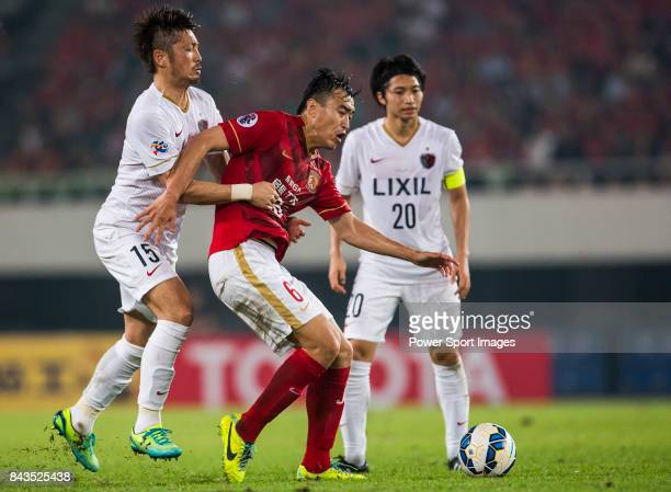 Kashima Antlers forward Takasaki Hiroyuki fights for the ball with Guangzhou Evergrande defender Feng Xiaoting during the AFC Champions League 2015...