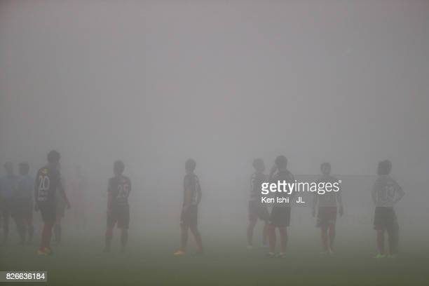 Kashima Antlers players stand as the match is suspended due to the heavy fog during the JLeague J1 match between Kashima Antlers and Vegalta Sendai...