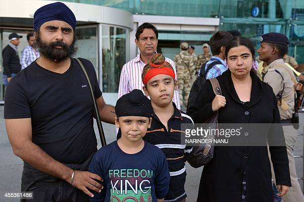 Kashmir floodevacuated Indian Sikhs Inderdeep Singh his wife Manpreet Kaur and children pose after arriving at the airport in Amritsar on September...
