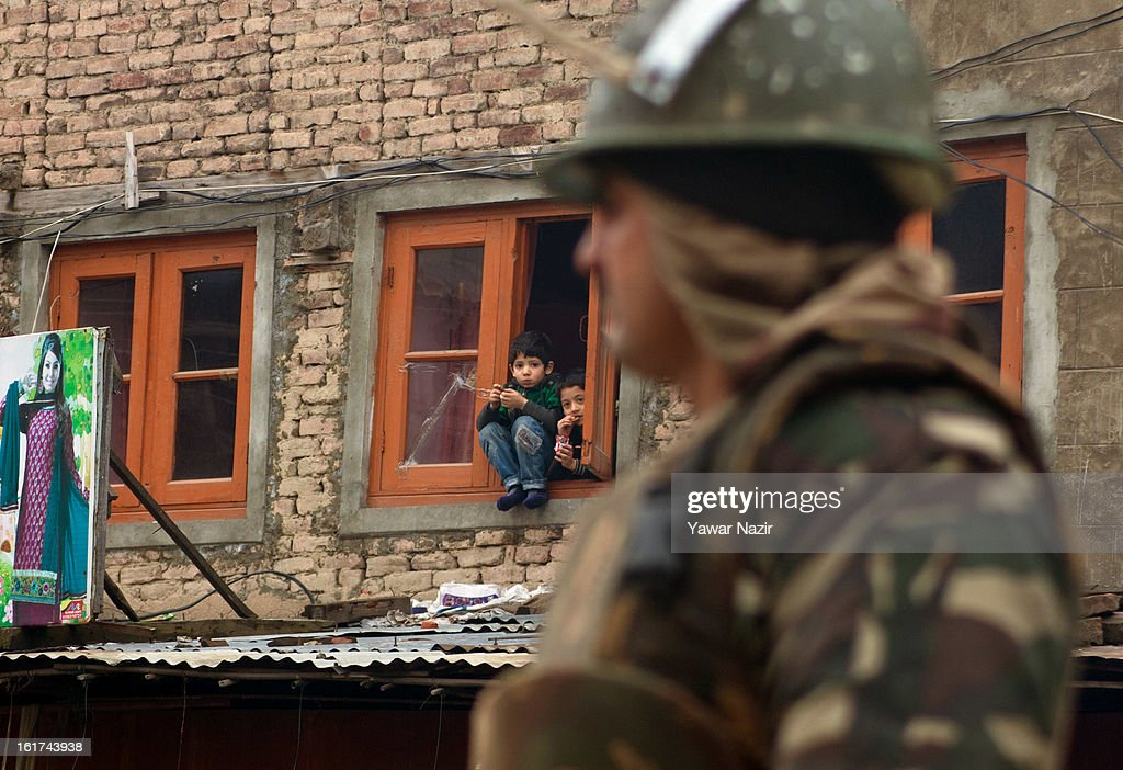 Kashmir Muslim Children look from the window of their house as an Indian paramilitary soldier stands guard during a strict curfew on the seventh consecutive day, imposed after the execution of alleged Indian parliament attacker Mohammad Afzal Guru on February 15, 2013 in Srinagar, the summer capital of Indian Administered Kashmir, India. Afzal Guru, from Sopore town in the north of Kashmir, was hung on February 09 for his role in the 2001 Indian parliament attack which left 14 dead. The hanging has further strained relations between India - who blamed the attack on 'Pakistan backed' militant group Jaish-e-Mohammed - and neighbouring Pakistan and has seen an military increase from both along the border.Curfew was lifted from some parts of Srinagar after four days.