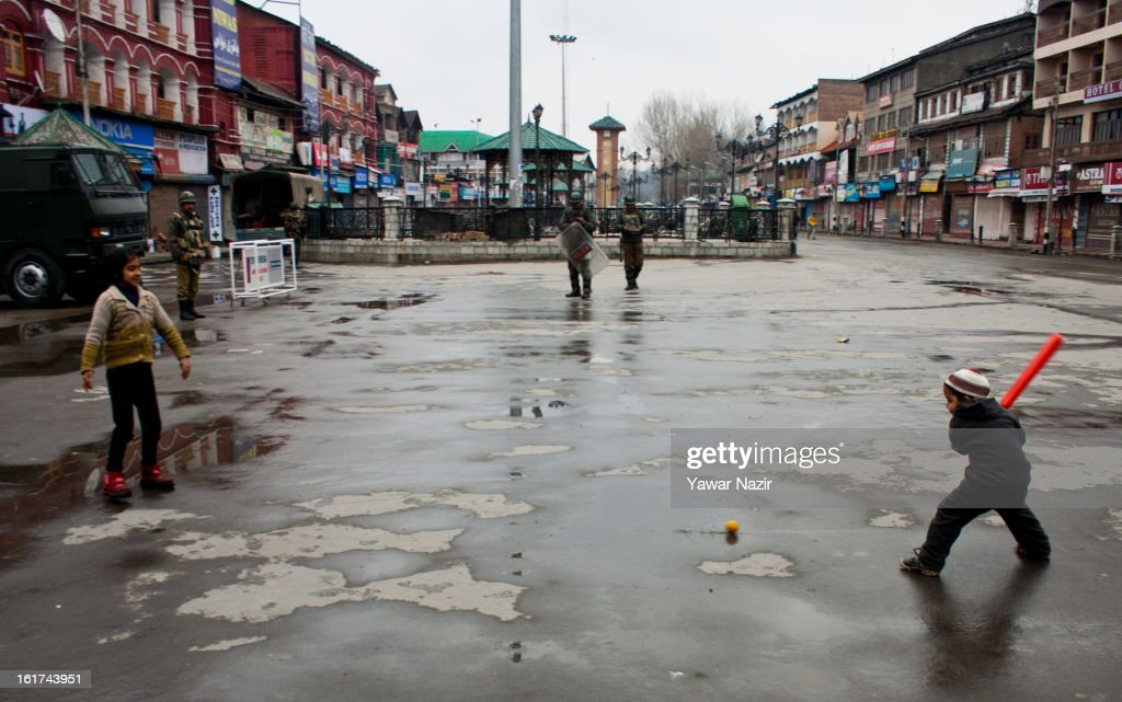 Kashmir Muslim children play cricket as Indian paramilitary soldiers patrol streets in city centre during a strict curfew on the seventh consecutive day, imposed after the execution of alleged Indian parliament attacker Mohammad Afzal Guru on February 15, 2013 in Srinagar, the summer capital of Indian Administered Kashmir, India. Afzal Guru, from Sopore town in the north of Kashmir, was hung on February 09 for his role in the 2001 Indian parliament attack which left 14 dead. The hanging has further strained relations between India - who blamed the attack on 'Pakistan backed' militant group Jaish-e-Mohammed - and neighbouring Pakistan and has seen an military increase from both along the border.Curfew was lifted from some parts of Srinagar after four days.