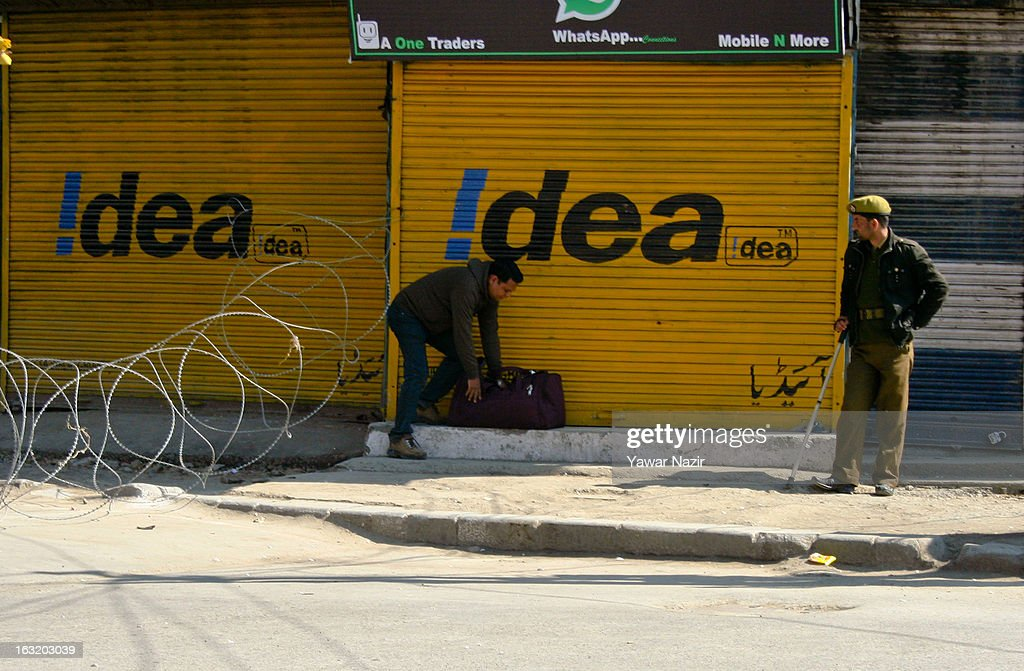 A Kashmir Muslim man tries to go through a concertina razor wire across the road by Indian police during a curfew like restriction on March 06, 2013 in Srinagar, the summer capital of Indian Administered Kashmir, India. Indian authorities imposed curfew like restrictions in most parts of Kashmir following a killing of kashmiri youth by Indian army in North Kashmir's Baramulla district yesterday.