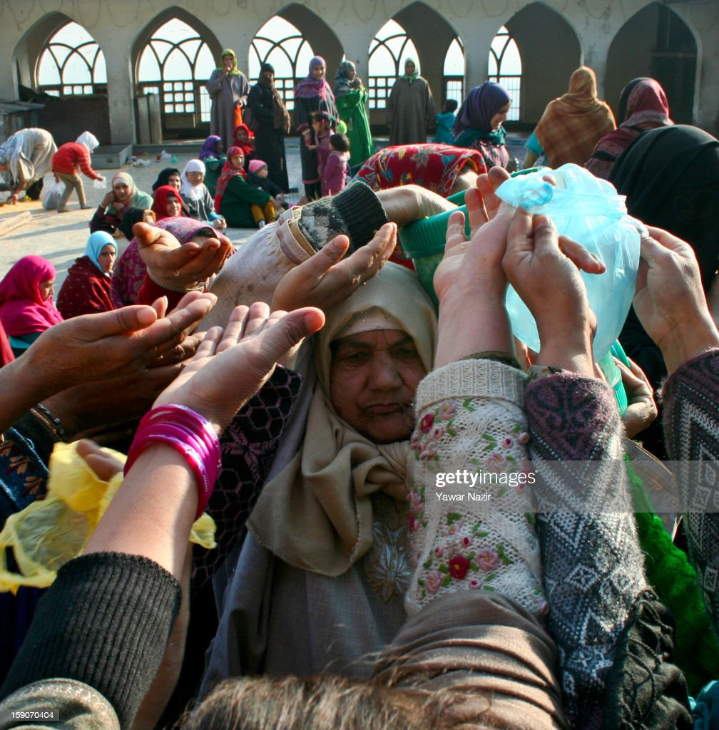 A Kashmir Muslim woman distributes food among Muslim devotees at the Shrine of the Sufi saint Sheikh Hamza Makhdoom during a festival on January 7, 2013 in Srinagar, the summer capital of Indian administered Kashmir, India. Thousands of Kashmiri Sufi Muslims make the pilgrimage to the shrine of Sufi Saint Sheikh Hamza Makhdoomi, also known as Makhdoom Sahib, to offer prayers on the anniversary of his birth.