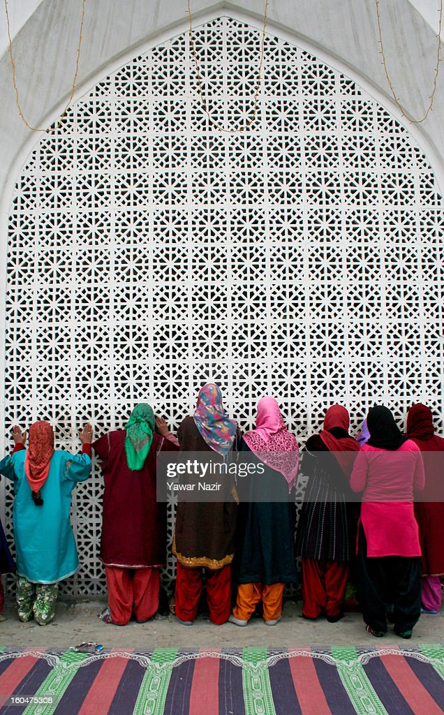 Kashmir Muslim women devotee ties a 'Desh', or a votive thread, to the fence at Hazratbal shrine on the Friday following Eid-e-Milad , or the birth anniversary of Prophet Mohammad on February 01, 2013 in Srinagar, the summer capital of Indian administered Kashmir, India. Thousands of Muslims from all over Kashmir visit the Hazratbal shrine in Srinagar to pay obeisance on the Friday following Eid-e-Milad , or the birth anniversary of Prophet Mohammed. The shrine is highly revered by Kashmiri Muslims as it is believed to house a holy relic of the Prophet Mohammed. The relic is displayed to the devotees on important Islamic days such as the Eid- Milad when Muslims worldwide celebrate.