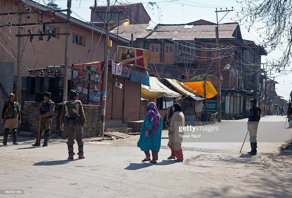 Kashmir Muslim women negotiate the curfew as Indian paramilitary soldiers stand guard during a curfew-like restriction on March 7, 2013 in Srinagar, the summer capital of Indian Administered Kashmir, India. Clashes erupted in most parts of Kashmir today leaving scores of people injured. Meanwhile Indian authorities imposed curfew-like restrictions for the second consecutive day in most parts of Kashmir following the killing of a Kashmiri youth by the Indian army in North Kashmir's Baramulla district.