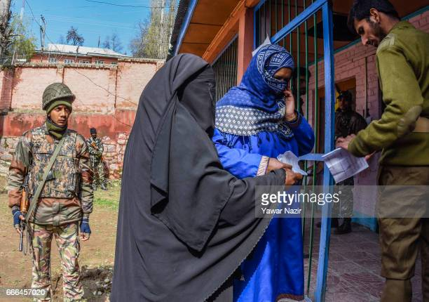 Kashmir Muslim women show their voting cards to an Indian policeman before entering a polling station to cast their votes during the elections of the...