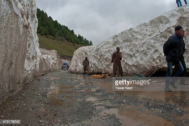 Kashmir pull their toboggan through the snowcleared SrinagarLeh highway on a treacherous pass after it was reopened by authorities on May 13 2015 in...