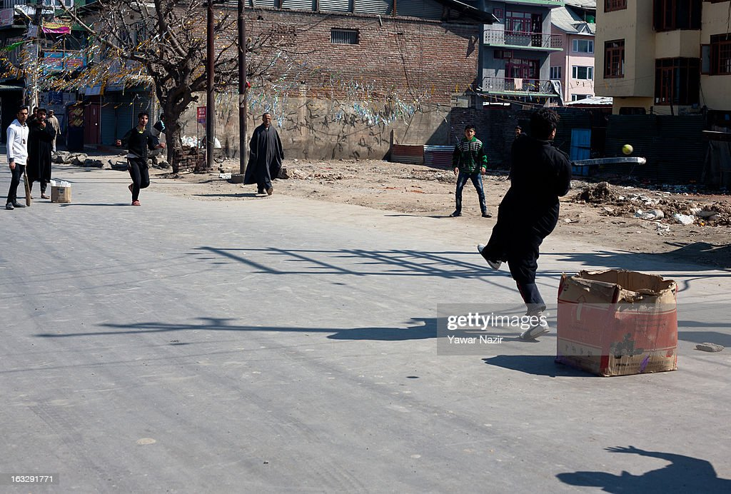 Kashmir teenagers play cricket on a road during a curfew-like restriction on March 7, 2013 in Srinagar, the summer capital of Indian Administered Kashmir, India. Clashes erupted in most parts of Kashmir today leaving scores of people injured. Meanwhile Indian authorities imposed curfew-like restrictions for the second consecutive day in most parts of Kashmir following the killing of a Kashmiri youth by the Indian army in North Kashmir's Baramulla district.