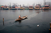 Kashmir woman rows a Shikara boat on a frozen Dal lake during a cold day on January 01 2015 in Srinagar the summer capital of Indian administered...