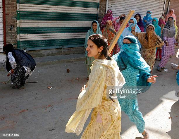Kashmir women tries to move in on Indian policemen with a stick during a protest against Indian rule on July 16 2010 in Srinagar the summer capital...