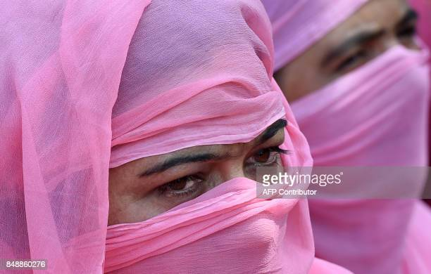 Kashmiri 'Anganwadi' a government sponsored child and mother care worker looks on during an antigovernment protest in Srinagar capital of the Indian...