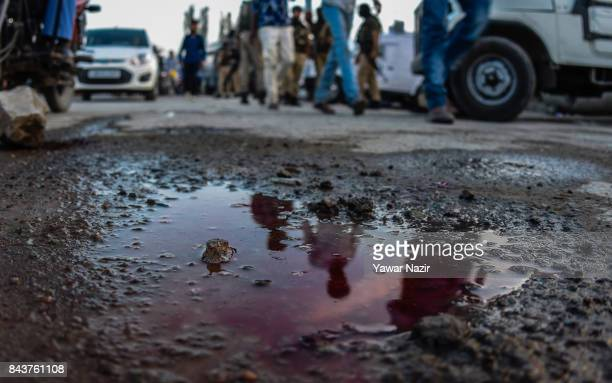Kashmiri are reflected on blood stains after a grenade attack by suspected militants in a busy market on September 7 in Srinagar the summer capital...