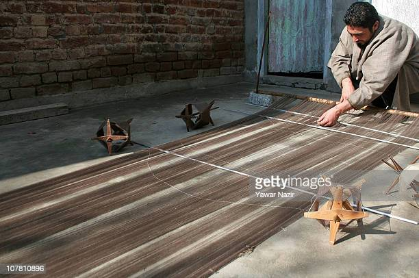 Kashmiri artisan collects pashmina threads used to make a pashmina shawl at his workshop on December 29 2010 on the outskirts of Srinagar the summer...